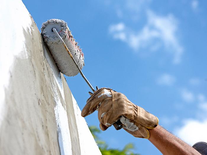 手袋をつけて外壁塗装中の男性